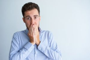 Shocked man with chipped tooth covers his mouth